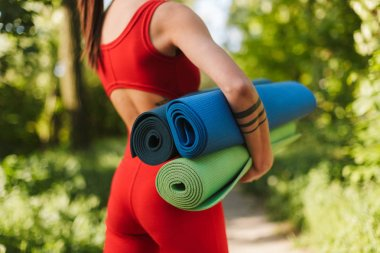 Close up photo of young woman body in red jumpsuit standing from back with colorful yoga mats in hands in park