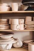 Fotografie Zavřít ručně vyráběné hliněné nádobí na dřevěných policích ve studiu keramiky