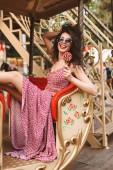 Fotografie Schöne Dame mit dunklen locken mit Sonnenbrille und Kleid Lolly pop Süßigkeiten in der hand halten und gerne auf der Suche in der Kamera während der Fahrt auf dem Karussell im Vergnügungspark
