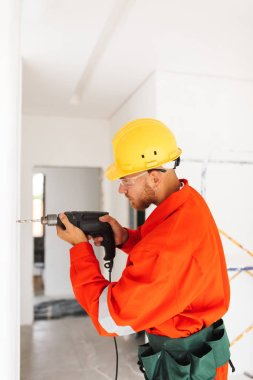 Young builder in orange work clothes and yellow hardhat using electric drill for making hole in wall