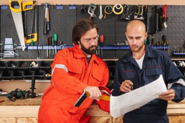Two builders in work clothes thoughtfully working on sketch plan with variety of tools on background in workshop