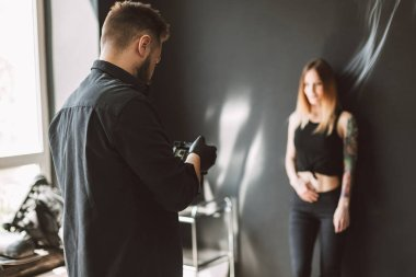 Professional tattooer taking photos on camera of tattooed girl standing on black background in modern tattoo studio