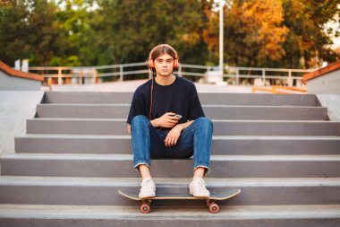 Young skater in orange headphones with cellphone in hands dreamily looking aside sitting on stairs at skate park