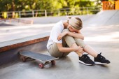 Young skater girl holding her painful leg and crying with skateboard near at skatepark