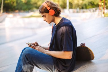 Young skater in orange headphones thoughtfully using cellphone with skateboard near at modern skatepark