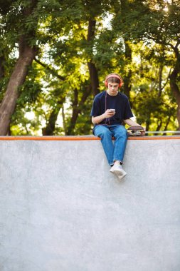 Young cool guy in orange headphones dreamily using cellphone with skateboard near spending time at modern skatepark