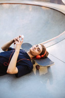 Young guy in orange headphones lying on skateboard with cellphone in hands happily looking in camera at skatepark isolated