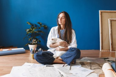 Pensive girl sitting on floor with drawings holding cute white cat in hands thoughtfully looking aside at home