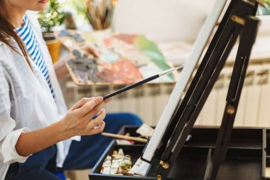 Close up painter drawing on easel holding palette color in hand at home
