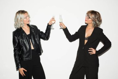 Two beautiful girls in black jackets with glasses of champagne in hands dreamily looking at each other over white background