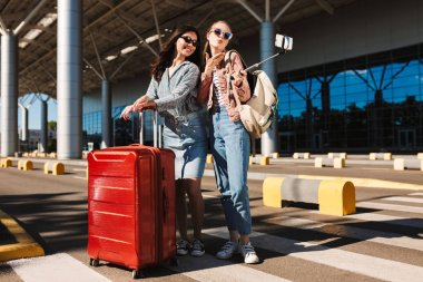 Pretty girls in sunglasses happily sending air kisses taking photos on cellphone together with red suitcase and backpack on shoulder outdoor near airport