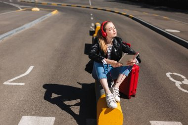 Cute girl in headphones listening music dreamily closing eyes with tablet in hand and red suitcase near on road of airport