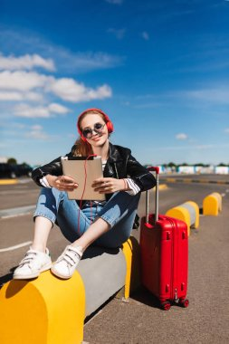 Smiling girl in sunglasses and headphones happily listening music on tablet with red suitcase near on road of airport