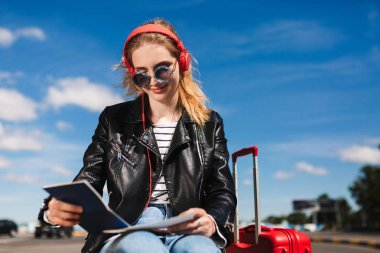 Beautiful smiling girl in sunglasses and headphones happily looking on passport with red suitcase near
