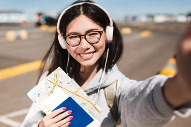 Portrait of smiling girl in eyeglasses and headphones happily looking in camera holding passport with ticket and map in hands near airport