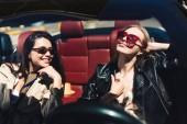 hübsche lächelnde Mädchen mit Sonnenbrille, die fröhlich Zeit miteinander verbringen, Cabriolet-Auto auf den Straßen der Stadt im Freien zu fahren