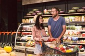 Fényképek Young guy and pretty girl with shopping list in hand dreamily looking at each other with trolley full of products in modern supermarket