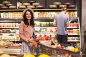 Fotografie Beautiful smiling girl in hat happily looking in camera with trolley full of products while guy on background choosing products in modern supermarket