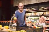 junger lächelnder Mann, der freudig in die Kamera blickt, Birne in der Hand haltend und Einkaufswagen voller Produkte in der Nähe, während hübsches Mädchen im Hintergrund Produkte im modernen Supermarkt auswählt