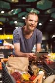 Junger Kerl lehnt an Einkaufswagen voller Lebensmittel und blickt freudig in die Kamera, hält das Tablet in der Hand in einem modernen Supermarkt