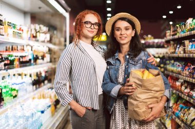 Beautiful girls with paper grocery bag full of products happily looking in camera spending time in modern supermarket