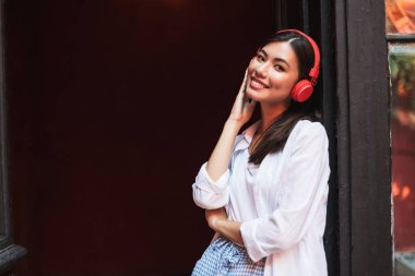 Pretty smiling girl in white shirt happily looking in camera leaning on old door listening music in red headphones