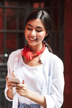 Joyful girl in white shirt and red headphones happily using cellphone outdoor