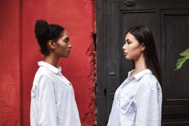 Young beautiful women in white shirts thoughtfully standing opposite each other isoalted
