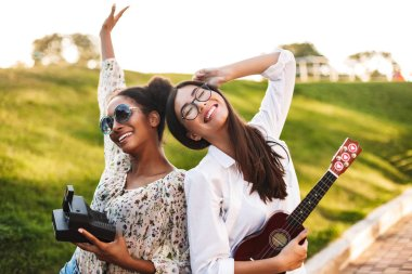 Cheerful girls with little guitar and polaroid camera in hands joyfully spending time together in park