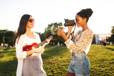 Beautiful girl taking photos on polaroid camera while pretty girl in sunglasses posing with little guitar in park