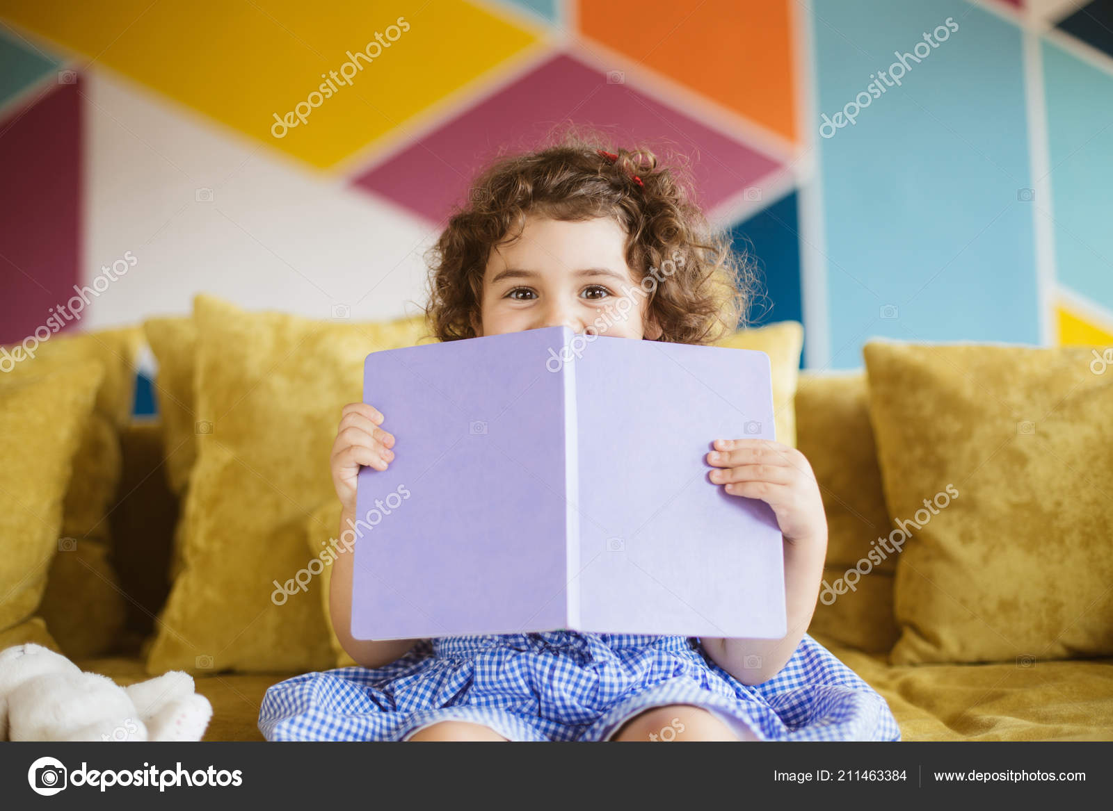 2c0c45a05 Nice baby girl with dark curly hair in blue dress happily looking in camera  covering mouth with book on sofa at home — Photo by ...
