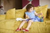 Cute usmívající se holčička s tmavými kudrnatými vlasy v modrých šatech s knihou na kolenou výběr barevné fixy na gauči doma