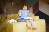 Fotografie Usměvavá holčička s tmavými kudrnatými vlasy v modrých šatech s knihou na kolenou šťastně výběr barevných fixů na gauči doma