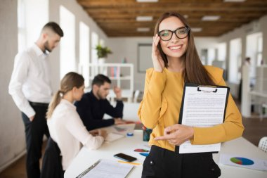 Young smiling business woman in eyeglasses happily looking in camera holding documents in hands in office with colleagues on background