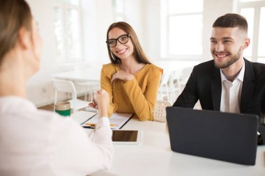 Smiling business woman in eyeglasses happily shaking applicant hand with business man near. Young joyful employers spending job interview in modern office