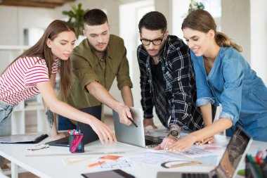 Young creative people working together with laptop. Group of cool guys working on new project spending time in modern office