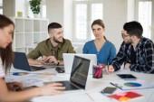 Mladých kreativních lidí s notebookem a Poznámkový blok v moderní kanceláři. Borci se o novém projektu společně trávit čas v práci