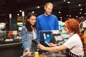 Fotografie Young smiling couple standing near cashier desk happily paying for products by credit card in modern supermarket
