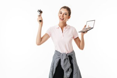 Young cheerful woman with make up brushes and palette in hands happily looking in camera over white background