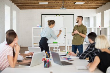 Young man in eyeglasses and shirt and pretty woman in blouse standing near board happily presenting new project to colleagues. Group of creative people working together in modern white office