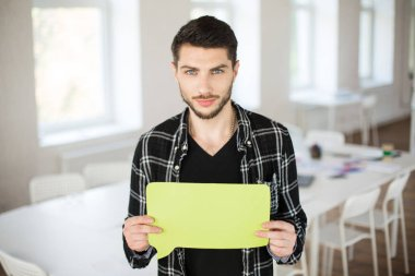 Young man in black short thoughtfully looking in camera holding yellow paper shape of message in hands at work in modern empty office