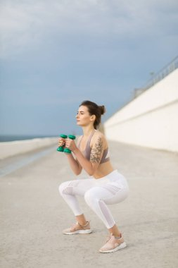 Young beautiful woman in sporty top and white leggings doing squats with dumbbells in hands dreamily looking aside outdoor
