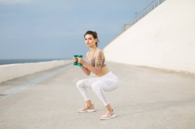 Young beautiful woman in sporty top and white leggings doing squats with dumbbells in hands thoughtfully looking in camera outdoor