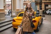 junge, fröhliche Frau im Trenchcoat mit kleiner schwarzer Kreuztasche, die eine Tasse Coffee to go in der Hand hält und Einkaufstüten in der Hand, die fröhlich beiseite schauen, mit gelbem Sportwagen im Hintergrund auf der Stadtstraße