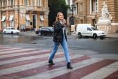 junge lächelnde Frau in Lederjacke und Jeans, die freudig in die Kamera blickt und eine Tasse Kaffee in der Hand hält, um auf der gemütlichen Stadtstraße zu gehen