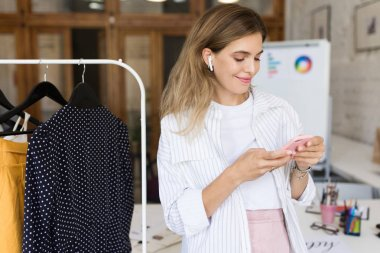 Pretty smiling girl in white shirt and wireless earphones happily using cellphone with clothes rack near at work in modern cozy office