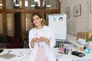 Beautiful smiling woman in white shirt and wireless earphones leaning on table joyfully looking in camera using cellphone at work in modern cozy office