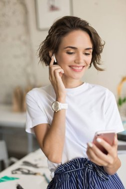 Young cheerful woman with short curly hair in wireless earphones sitting on desk happily using cellphone at work in modern office