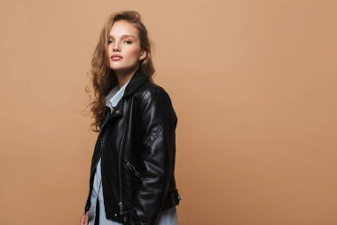 Beautiful girl with wavy hair in black leather jacket and shirt dreamily looking in camera over beige background