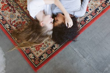 Beautiful girl with blond hair and pretty girl with dark curly hair dreamily lying on vintage carpet together at home